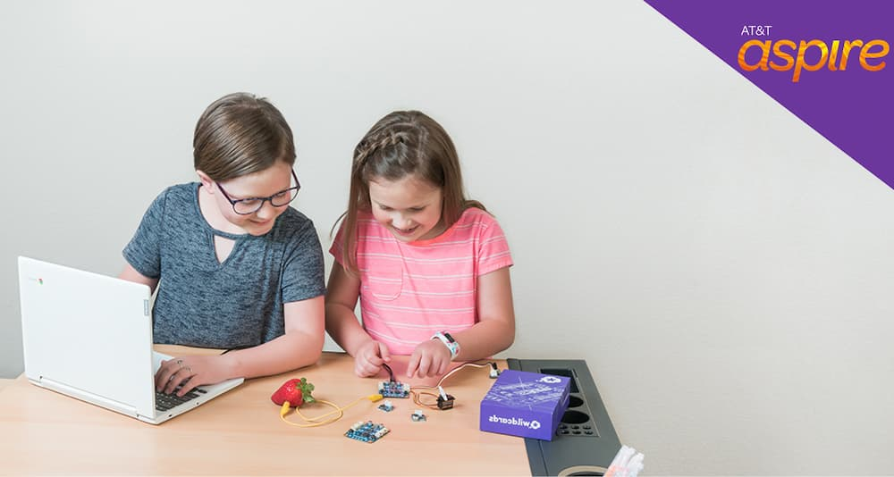 Girl in glasses making STEM projects with circuit cards